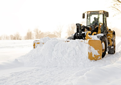 industrial equipment plowing snow, as part of commercial snow removal companies in Bartonville IL